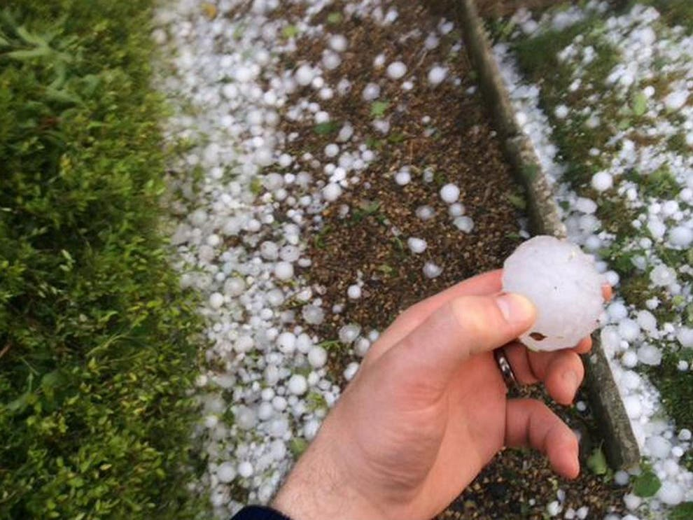Large Hailstorm with hand holding hail
