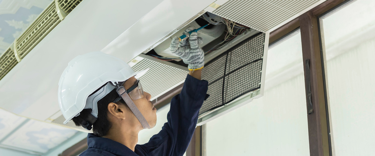 air conditioner repair man checking air conditioning system