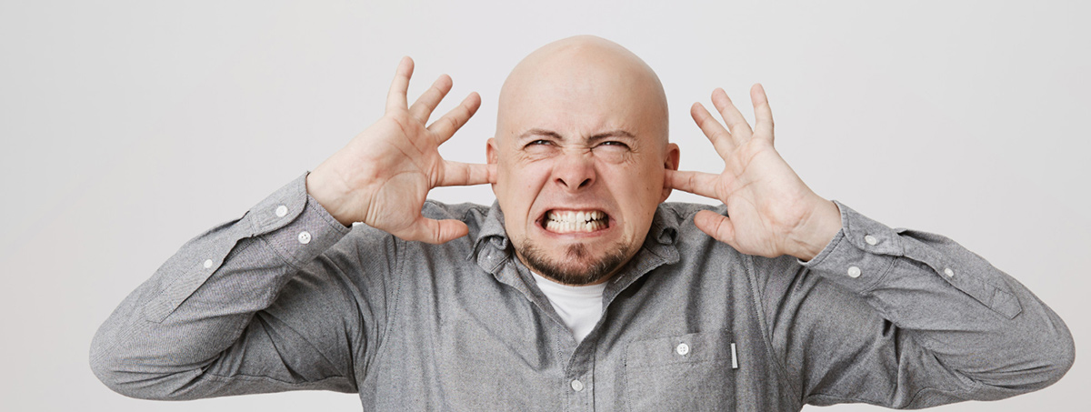 angry bothered bald guy shut ears with fingers