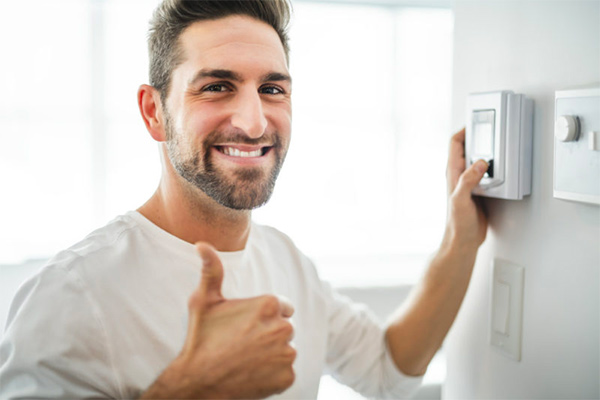 Man using a programmable thermostat
