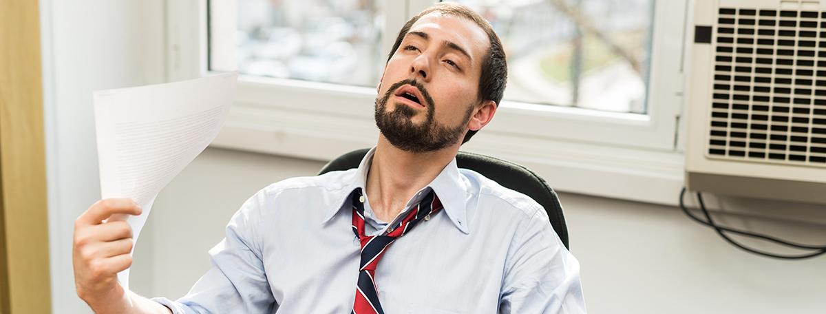 man fanning himself broken air conditioner in office