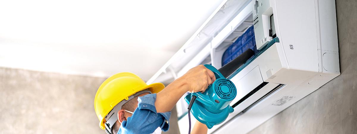 maintenance man doing air conditioner maintenance on wall AC unit