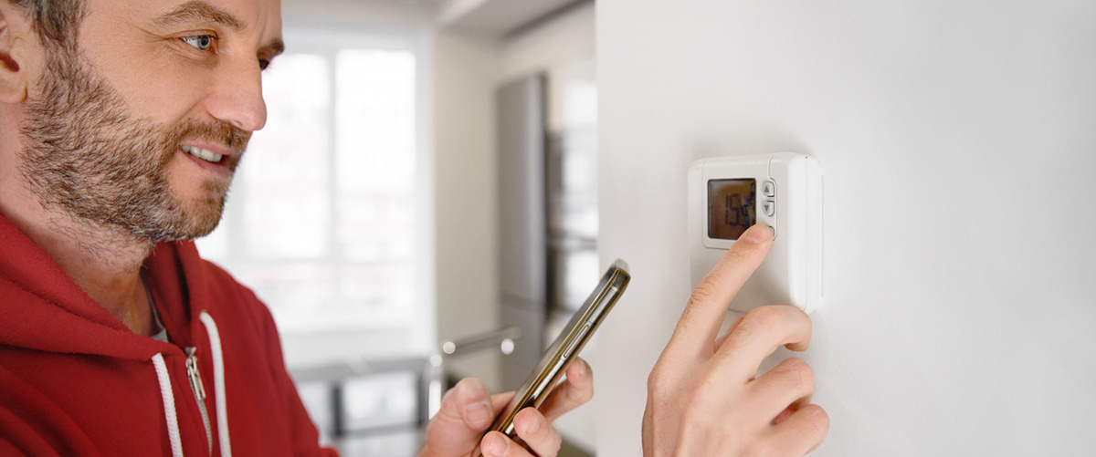 man looking his smartphone how temperature heater is regulated