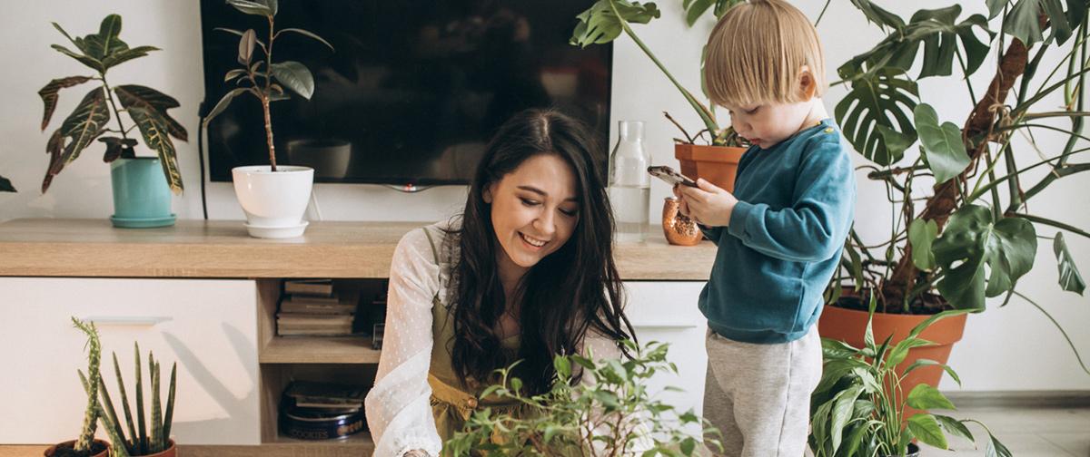 mother with little son cultivating houseplants