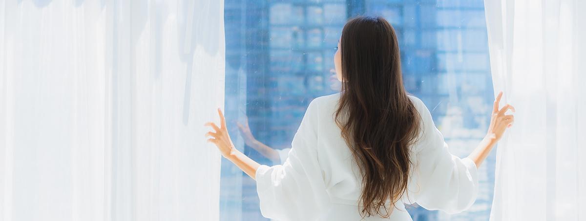 beautiful young woman closing curtains