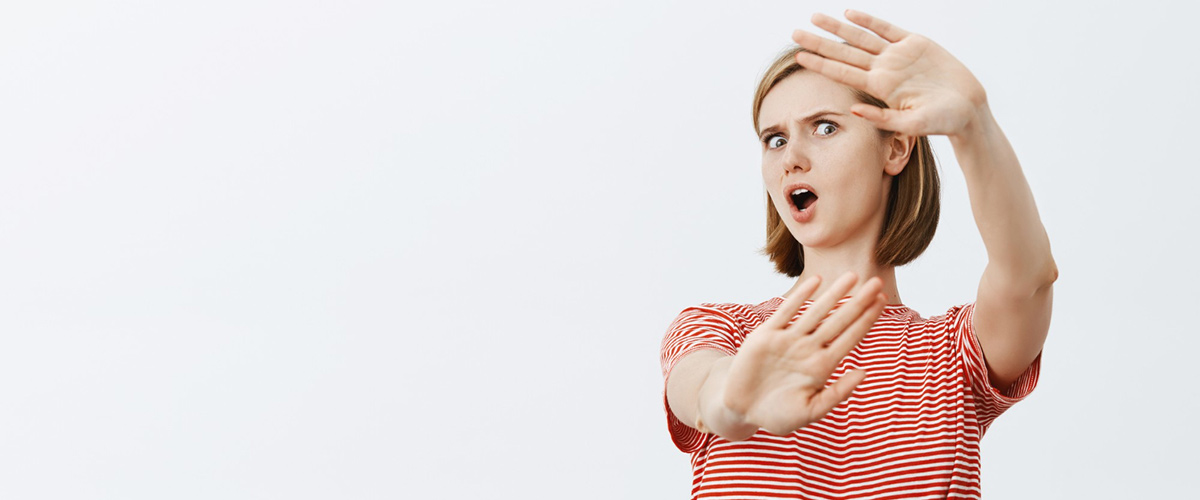 shocked freak out young woman raising hands defensive protecting herself