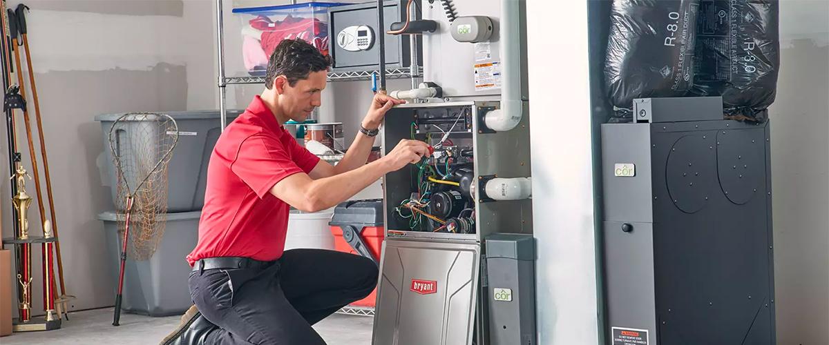 HVAC technician doing furnace maintenance in Denver home