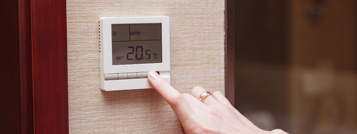 woman switching digital thermostat